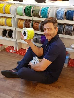 Creative Lamps: marca de luminárias customizáveis é inaugurada no Rio de Janeiro. foto do empresario Fabio segurando um rolo de fio amarelo.