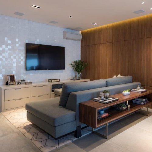 sala de tv com parede revestida em madeira por Patricia Pasquini