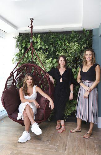 Spaço Interior assina projeto da casa nova da influenciadora Mari Saad, no portal Conexão Décor. Mari Saad sentada no balanço com design de Sergio Mattos, as arquitetas em pé tendo ao fundo uma parede verde.