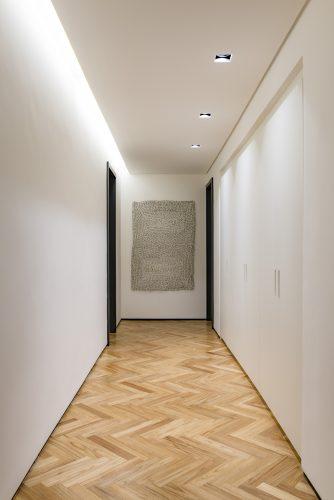 Corredor branco com portas pretas no ambiente de Consuelo Jorger
