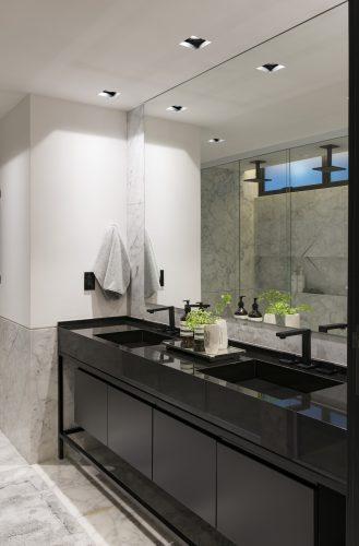 banheiro com armario e bancada preta assinada por Consuelo Jorge