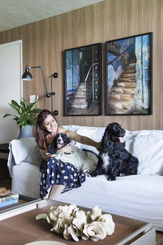 Carmen Mouro na sala com sofa branco e cachorros
