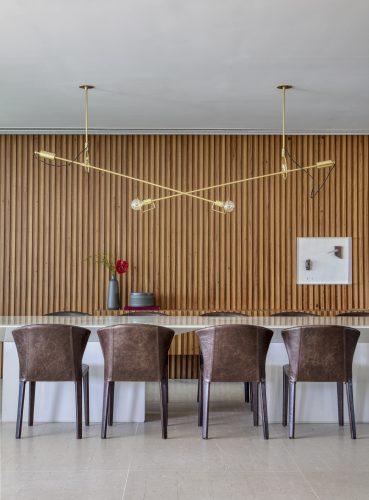 Sala de jantar com lustre de Jader Almeida, assinada por Studio MH
