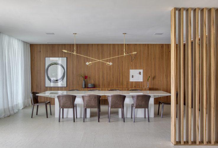 sala de jantar com madeira ripada e mesa branca assinada por Studio MH