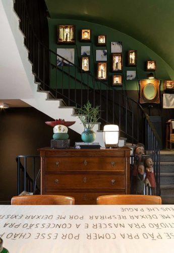 Decorando a parede da escada. Parede pintada de verde musgo com fotos penduradas.