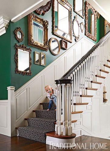 Decorando a parede da escada. Coleção de espelhos na parede verde .