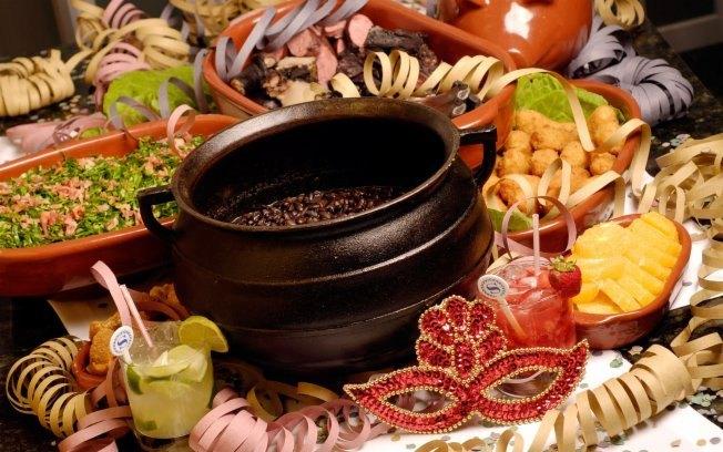 Décor para receber no Carnaval com Feijoada, o match que dá o maior samba. Mesa de feijoada enfeitada com serpentina e mascaras.