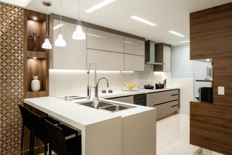 Cozinha branca e marrom com ilha e bancada.