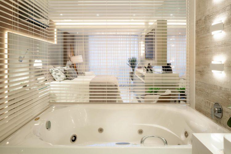 Banheira separada do quarto com vidro e persiana.