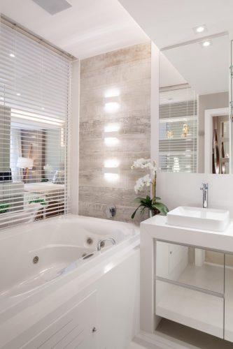 Banheira separada do quarto por vidro e persiana.