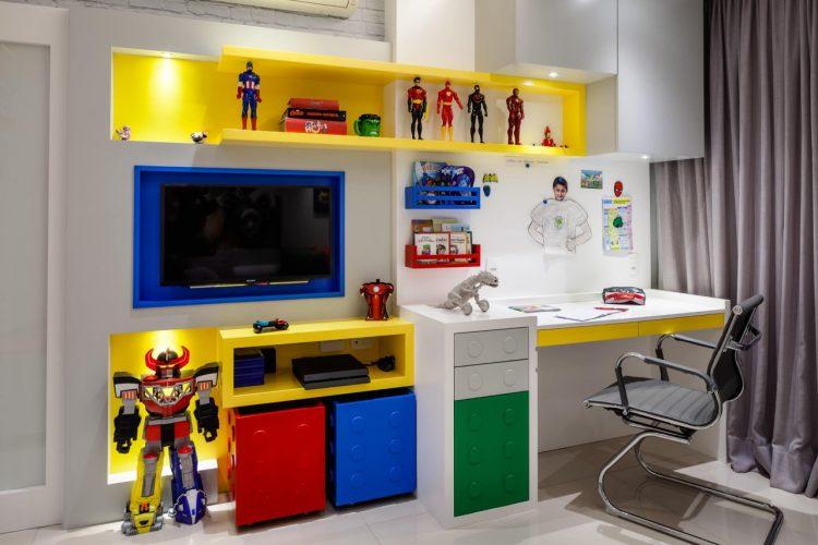 Estante de quarto de menino com nichos amarelo, azul e vermelho tendo o Lego como tema.