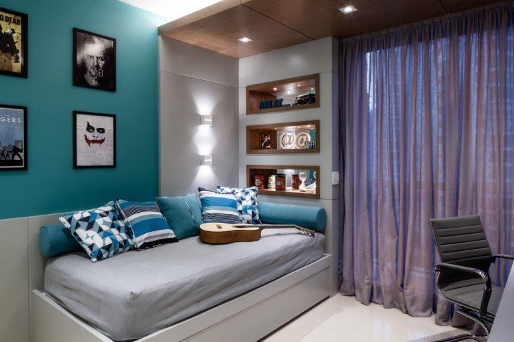Quarto de adolescente em tons de conza e azul, com cama encostada na parede e nichos laterias iluminados.