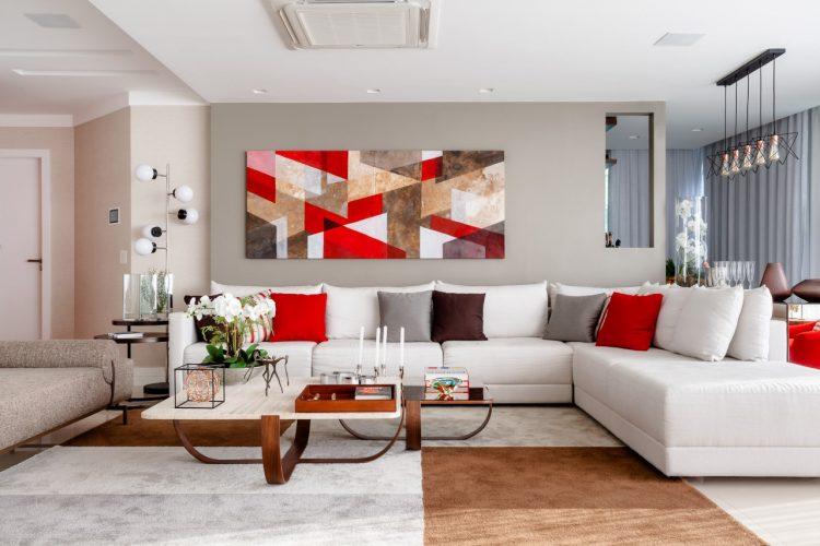 Sofá em L na cor branca, almofadas nas cores vermelho, preto e cinza.