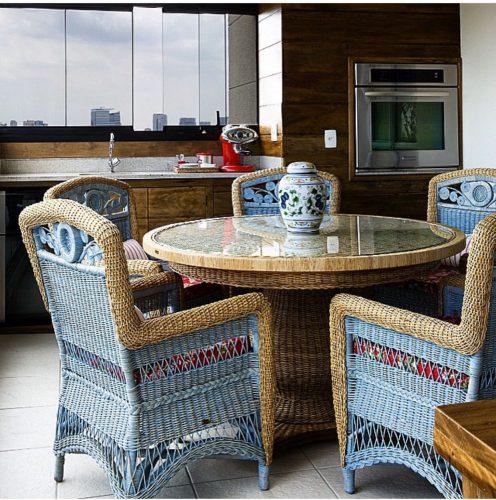 Outlets de decoração, loja Armando Cerello. Cadeiras em vime natural e pintado de azul em volta de uma mesa redonda em vime natural.
