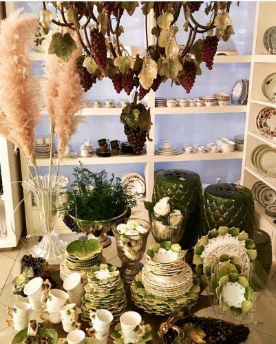 Outlets de decoração, loja Star Home. Interior da loja com mesa repleta de porcelanas em verde e branco;