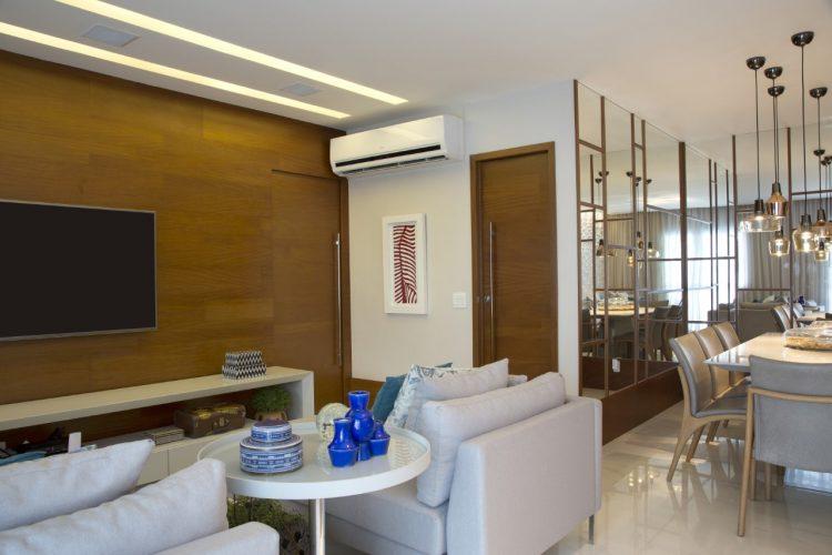 APARTAMENTO SOFRE MUDANÇA NA PLANTA PARA TER MAIS AMPLITUDE. Revestimento em madeira na parede do home tv e espelho na sala de jantar.