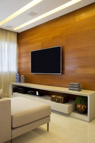 APARTAMENTO SOFRE MUDANÇA NA PLANTA PARA TER MAIS AMPLITUDE. Parede do home tv revestida em madeira