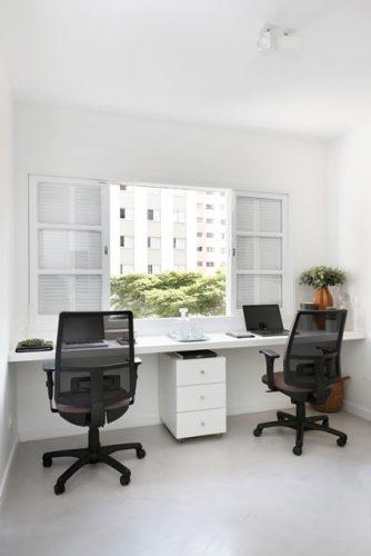 Apartamento de  95 m² e  40 anos ganha atmosfera moderna após reforma. Bancada embaixo na janela no escritório.
