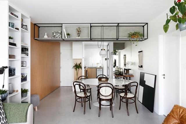 Apartamento de  95 m² e  40 anos ganha atmosfera moderna após reforma. Na viga, uma estante de ferro e a cozinha aberta para a sala.