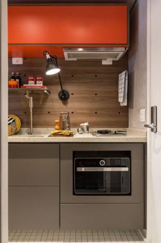 Cores vivas no décor com pegada industrial. Bancada de cozinha com cooktop embutido e nicho laranja em cima.