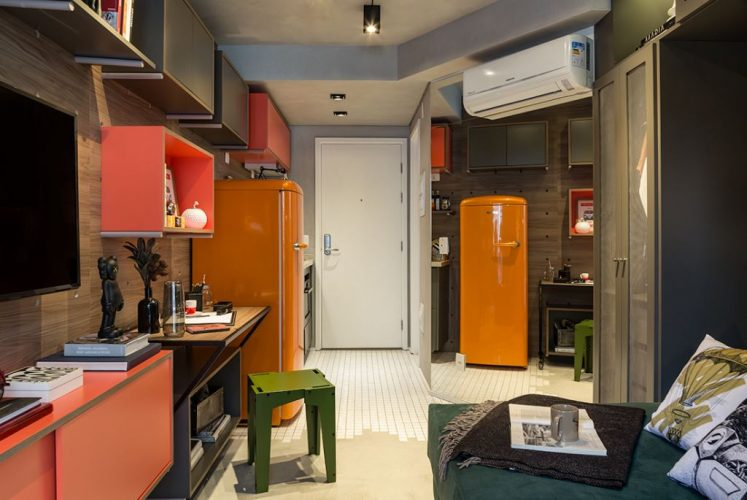 Cores vivas no décor com pegada industrial. Apartamento compacto com geladeira laranja e piso em cimento.