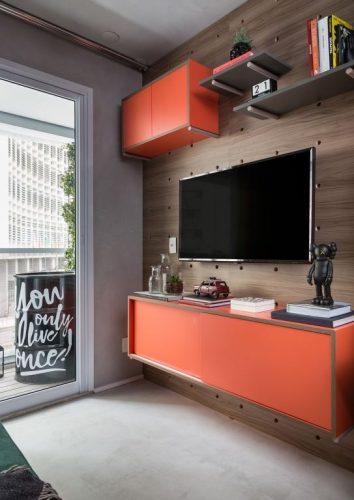 Cores vivas no décor com pegada industrial. Painel da tv em medeira e nichos na cor laranja