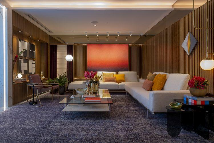 PATRICÍA HAGOBIAN ASSINA LINIE LOUNGE. Living com sofás brancos e parede em madeira ripada
