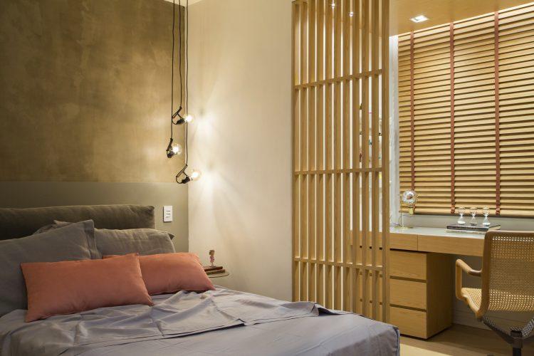 quarto com cama, divisória de madeira ripada e escritório em madeira no projeto de decoração de Monique Pampolha e Hannah Cabral