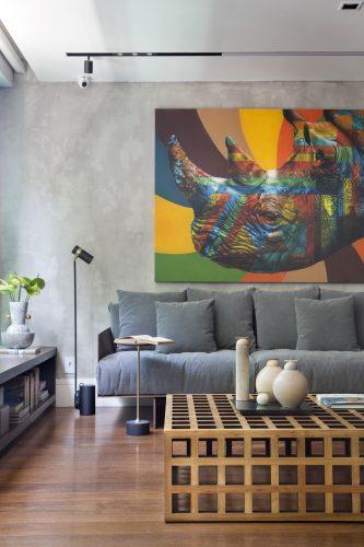 Sofa cinza embaixo do quadro de rinoceronte no apartamento assinado por Monique Pampolha e Hannah Cabral