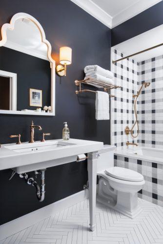 Xadrex na decoração. Banheiro com a parede de funda da banheira revestida com revestimento xadrez em preto e branco