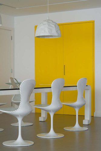DICAS EM COMO USAR PORTAS COLORIDAS. Sala de jantar com paredes brancas e porta amarela.