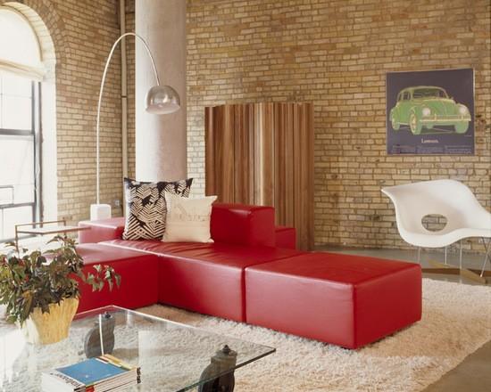 Os Signos e suas cores na decoração. Áries é a cor vermelha.Sala com parede em tijolinhos e sofá vermelho.