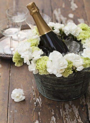 Recebendo com vinho. Balde de gelo com champanhe e flores