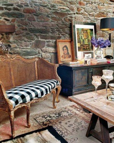 Xadrex na decoração. Ambiente com parede de pedra e sofá em palhinha com tecido xadrez