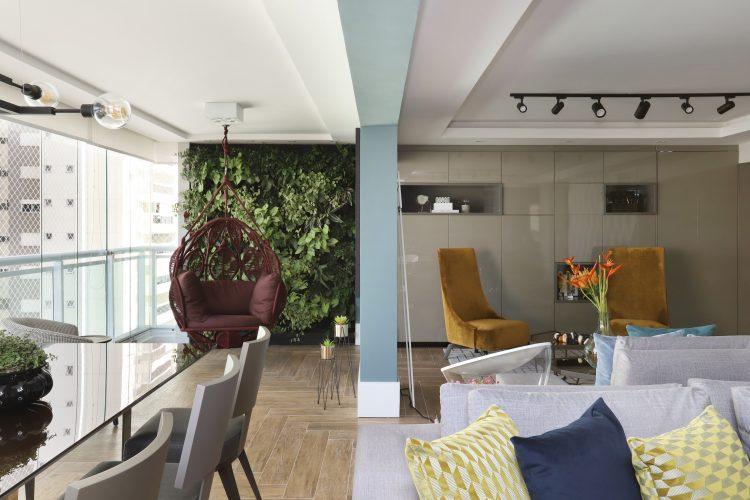 Decór Naturalista: Verde que te quero verde. Varanda integrada ao apartamento recebeu uma poltrona de balanço vinho pendurada ao teto e a parede verde ao fundo