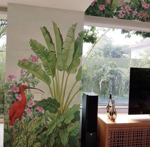 Decór Naturalista: Verde que te quero verde. Sala com janelão para a piscina , tendo a parede com uma pintura feita á mão . Pintura de palmeira e uma garça rosa.