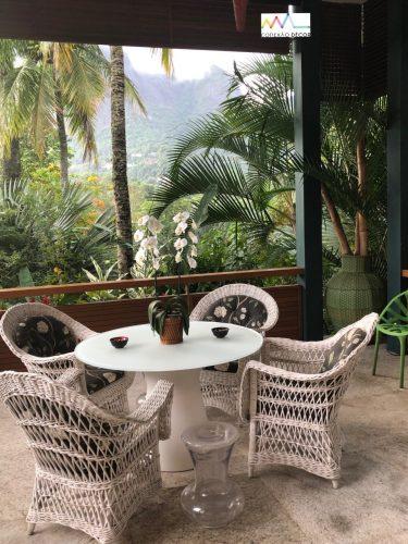 Decór Naturalista: Verde que te quero verde. Arquitetura integra exterior com interior, varanda aberta de uma casa  com mesa e cadeiras e ao fundo vegetação