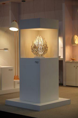 Luminária de mesa  em cima de uma base para exposição na feira