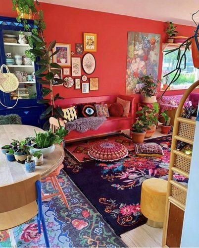 Estilo de decoração, Maximalismo, explosão de cores na sala com parede vermelha e vários tapetes estampados.