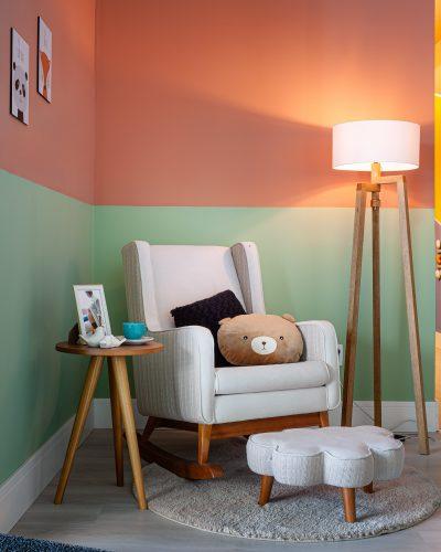 Quarto inspirado no filho da atriz e influencer Jade Seba. Poltrona para amamentação branca com um puff na frente e paredes pintadas em duas cores, menta e siena, dividindo ao meio.