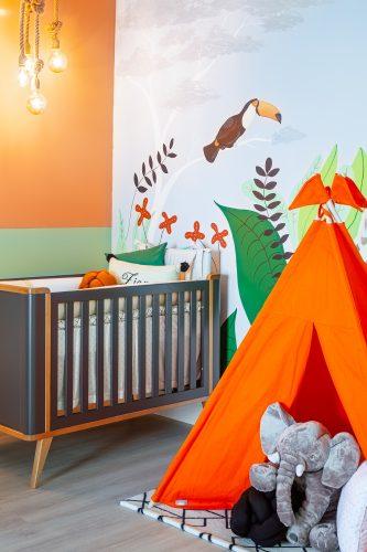 Quarto inspirado no filho da atriz e influencer Jade Seba. Berço preto, cabaninha infantil laranja, parede pintada á mão com tema de floresta e parede lateral pintada em duas cores, meta e siena.
