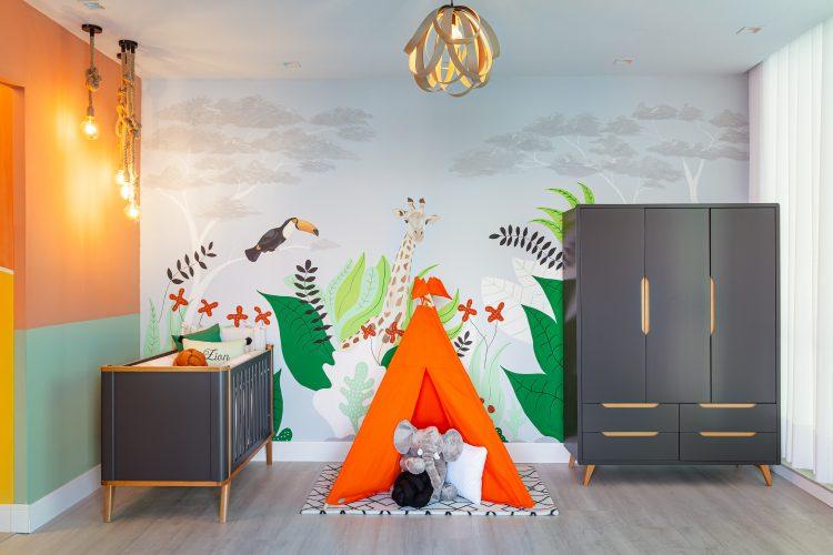 Quarto inspirado no filho da atriz e influencer Jade Seba.Quarto infantil com a parede ao fundo pintada á mão com tema de floresta, uma cabana laranja e um armário preto