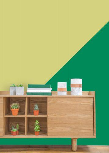 Verde cítrico é a cor do mês de agosto da Sherwin-Williams. Parede pintada em duas cores, verde cítrico e verde escuro com buffet em madeira na frente.