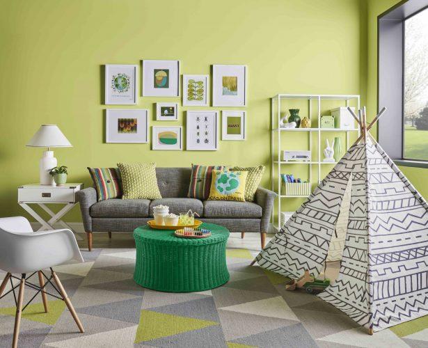 Verde cítrico é a cor do mês de agosto da Sherwin-Williams. Sala com sofá cinza e a parede de fundo do sofá com quadros e parede pintada com verde cítrico
