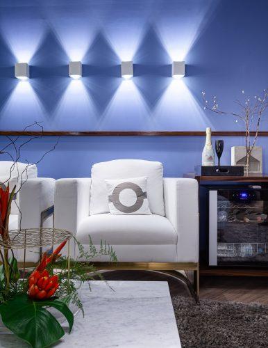 Feng Shui na sala zen, parede azul com luminárias e poltrona branca