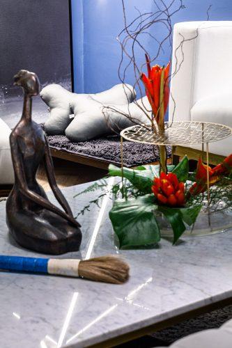 Feng shui na sala zen, mesa de centro com flor tropical  e um pincel chines