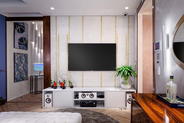 Feng Shui, na sala zen. Televisão na parede que tem filetes dourados para enfeitar e rack branco