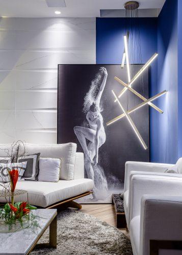 Sala zen , grande luminária metálica no canto pintado de azul e um quadro preto e branco de uma bailarina