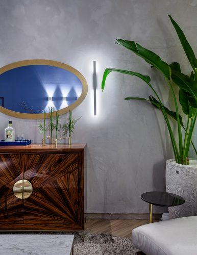 Feng Shui na sala zen, espelho oval em cima de uma comoda em madeira e planta alta
