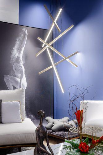 Sala zen, luminária de metal criando  uma escultura, tapete para cachorro embaixo e ao fundo parede azul